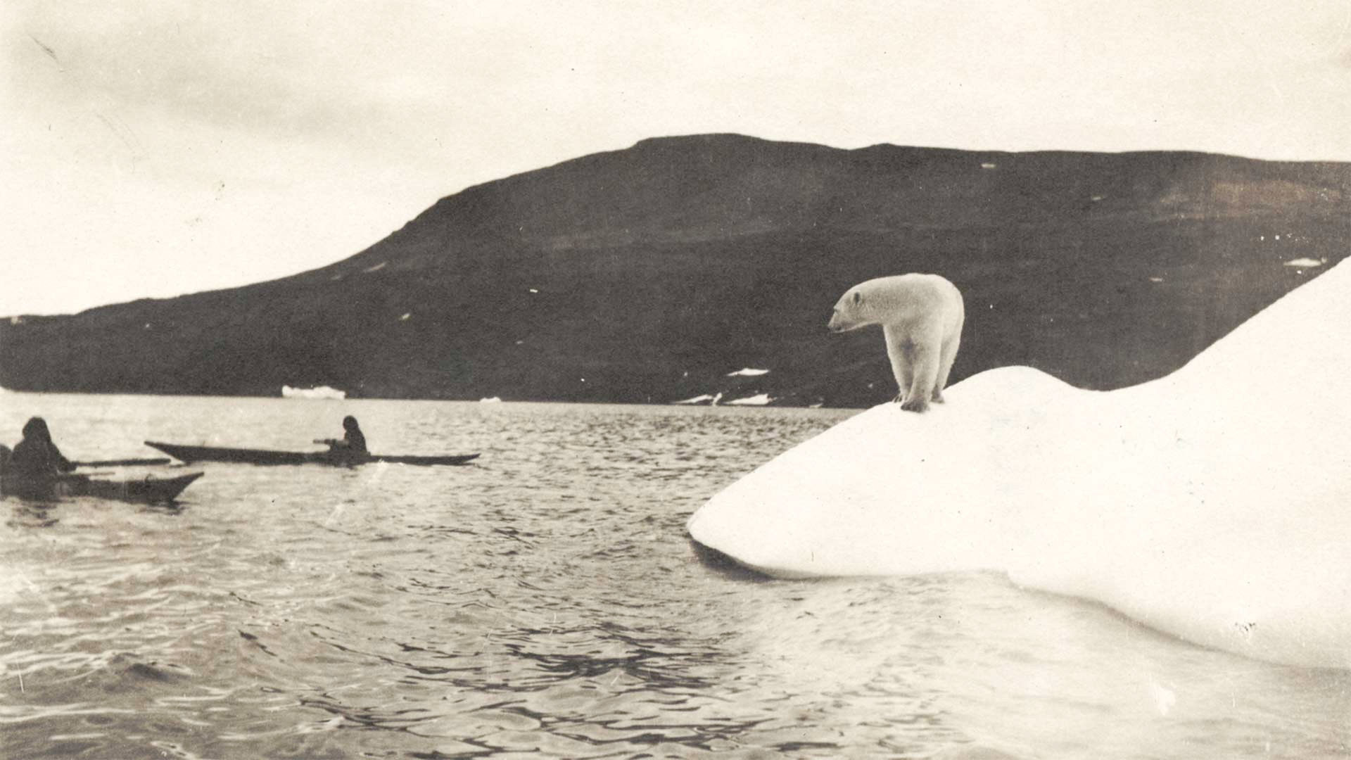 Vintage photo of a polar bear on a piece of ice looking at two people in long canoes