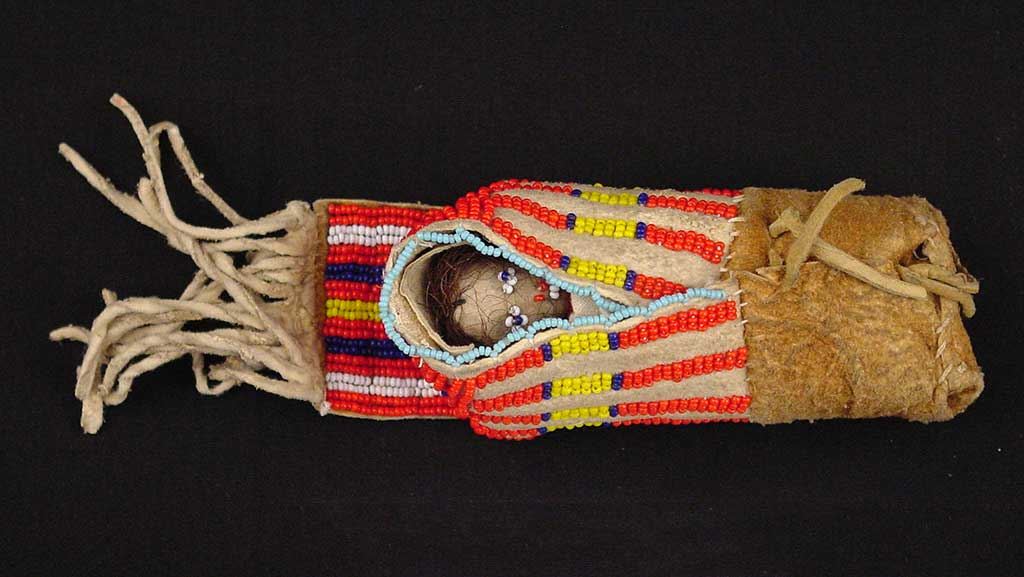 small doll with tiny blue eyes wrapped up in a blanket decorated with red, yellow, and blue beadwork