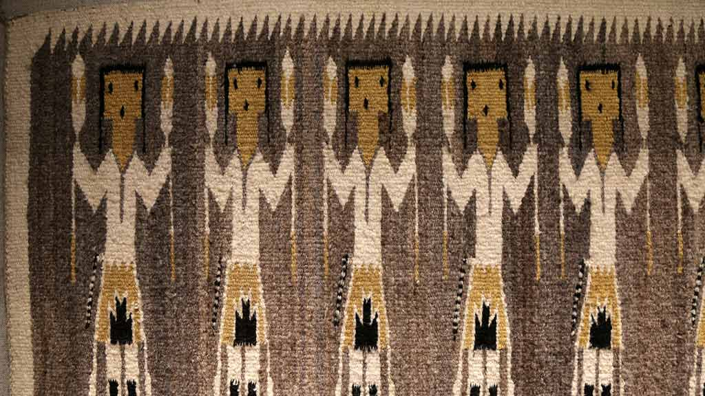 rug with repeated design of people holding long objects that look like torches