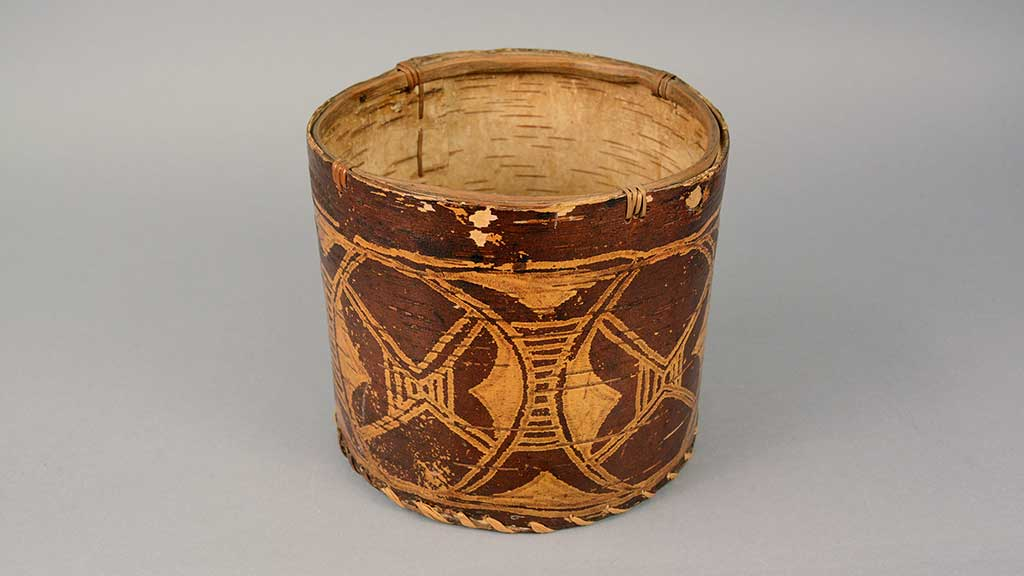 cylindrical solid basket with maroon and gold designs around the circumference