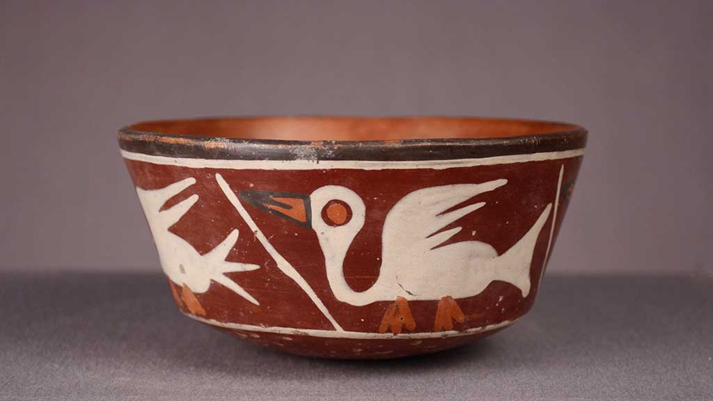 red ceramic bowl with graphic white bird motif