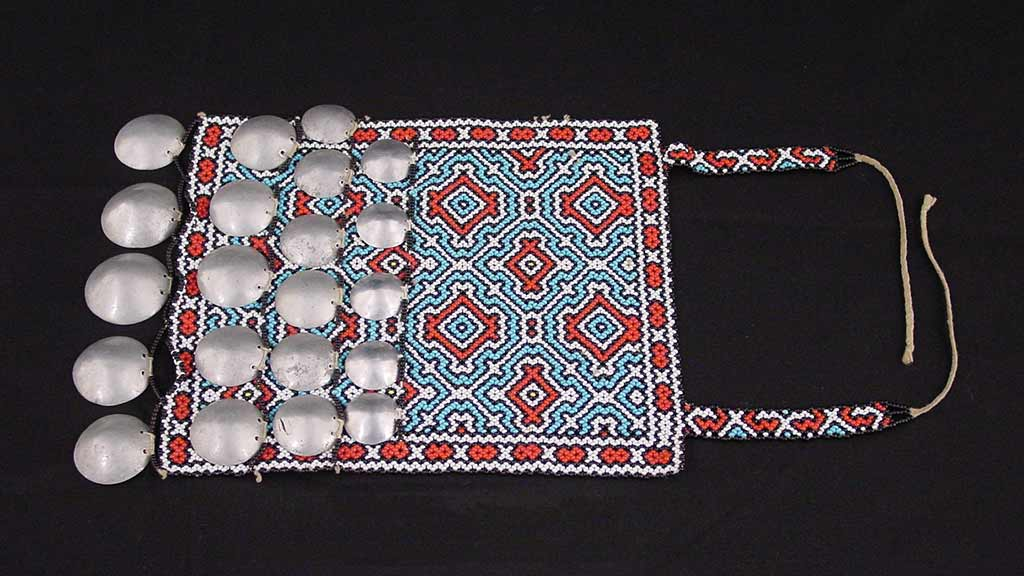 flat cloth with white, blue, and red geometric design, silver discs, and two strings