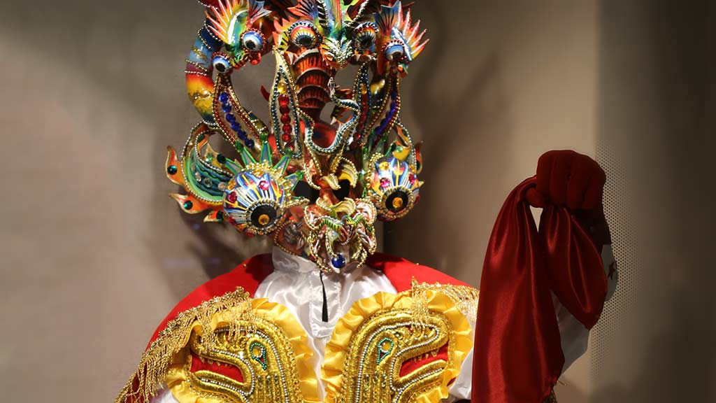 brightly colored festival costume with golden reptile design and many-eyed detailed devil mask