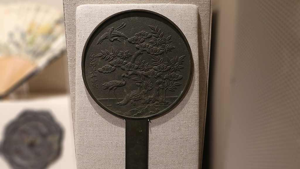 round dark metal mirror with relief of water fowl