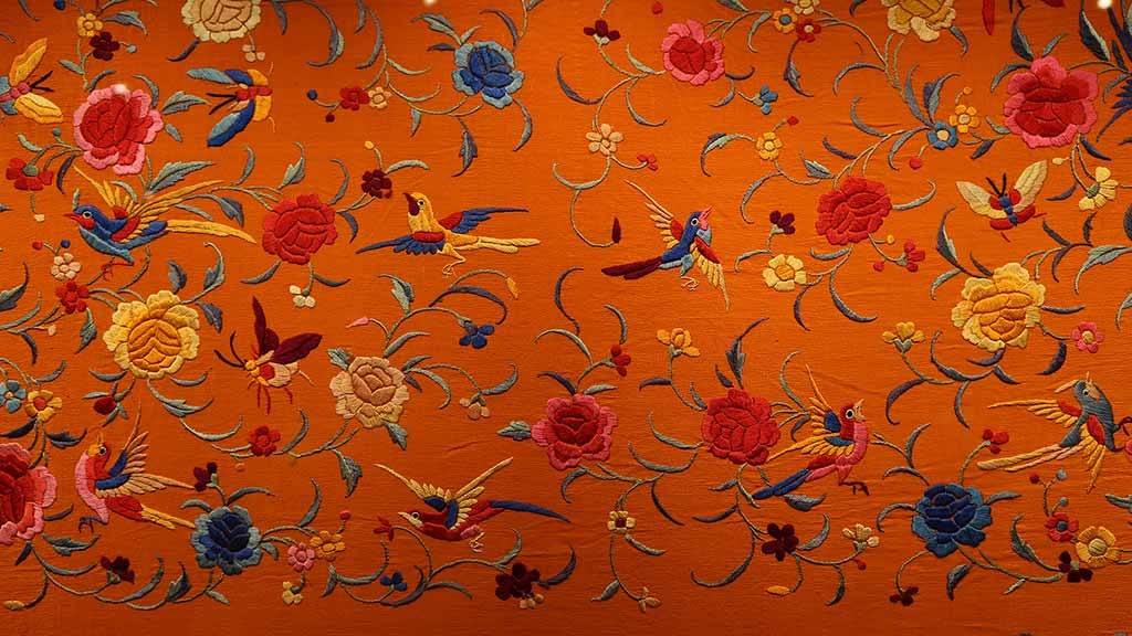 orange textile with embroidered flowers and birds