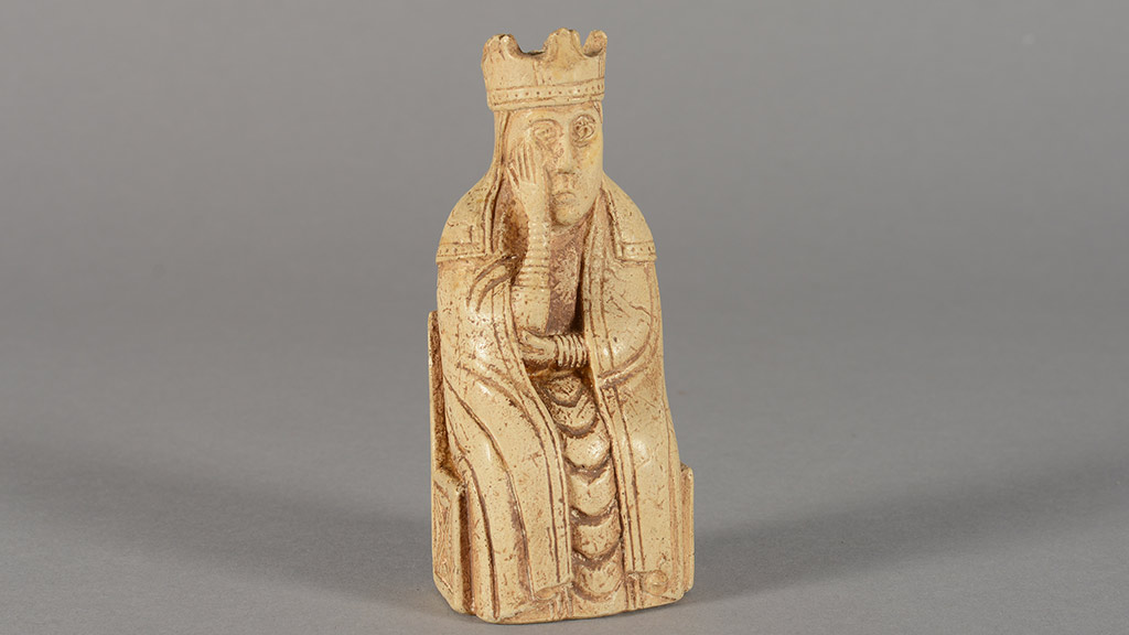 Cream-colored chess piece. A king holds his face wearily.