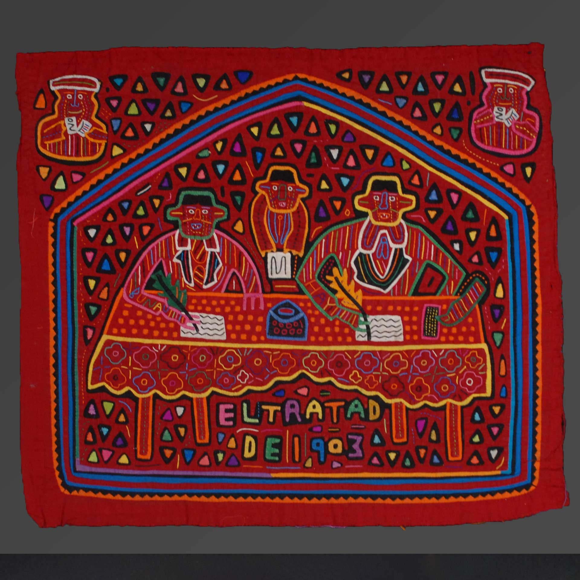 red cloth square with colorful stylized embroidery of three men seated at a table signing a document