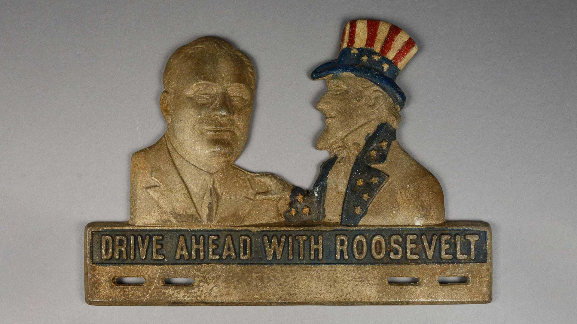 license place attachment with Uncle Sam with his hand on Franklin D. Roosevelt's shoulder and the words Drive Ahead With Roosevelt
