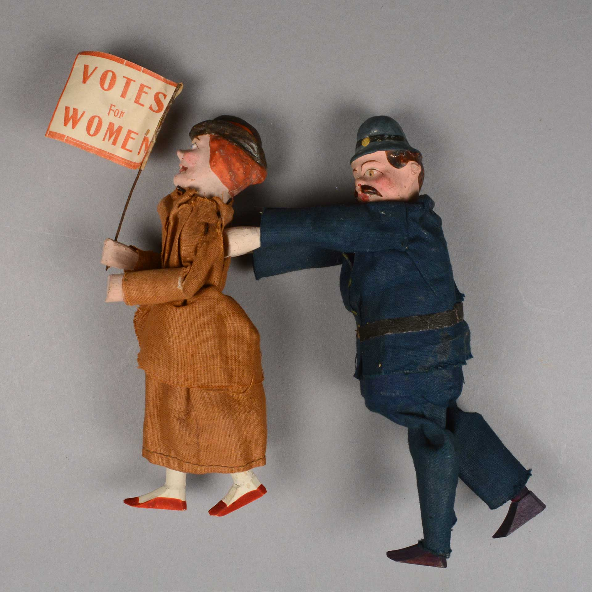 vintage figure of a police officer pushing a woman who has a flag that says Votes For Women in her hand