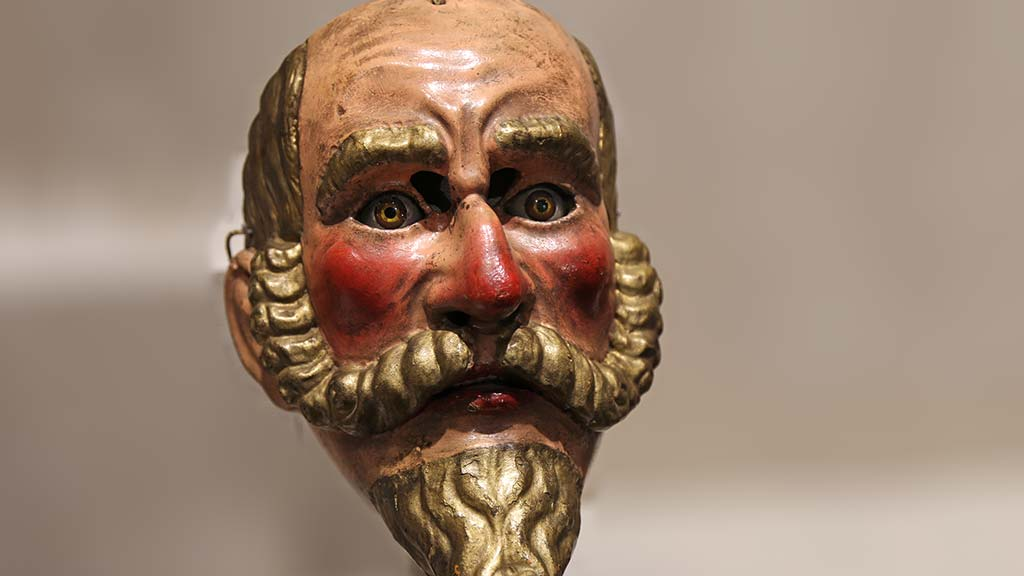 lifelike human mask with rosy cheeks and a long mustache and beard