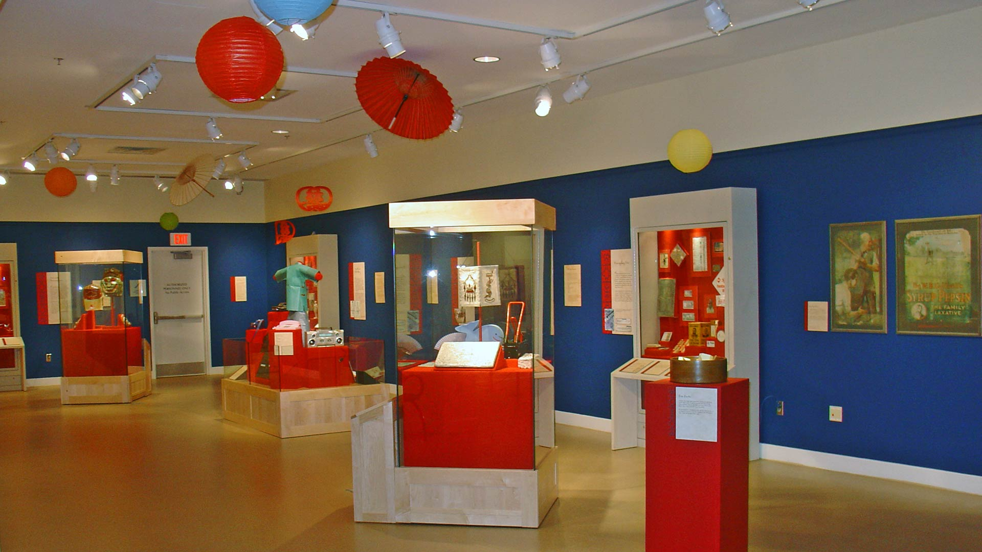 gallery overview, red paper lantern and umbrella, ocean blue walls, display stands