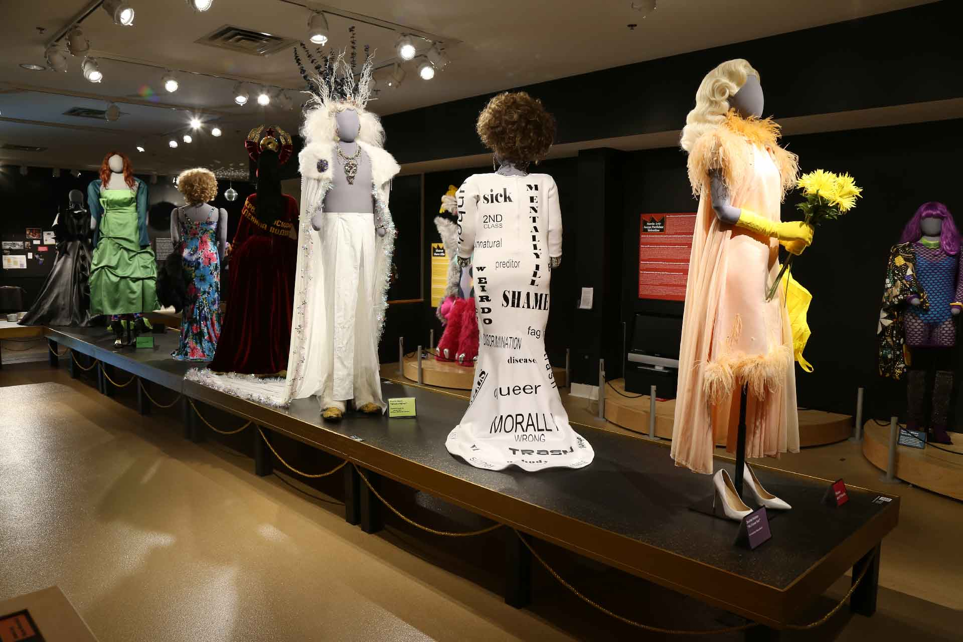back view of exhibit featuring mannequin in pink drag costume in the front