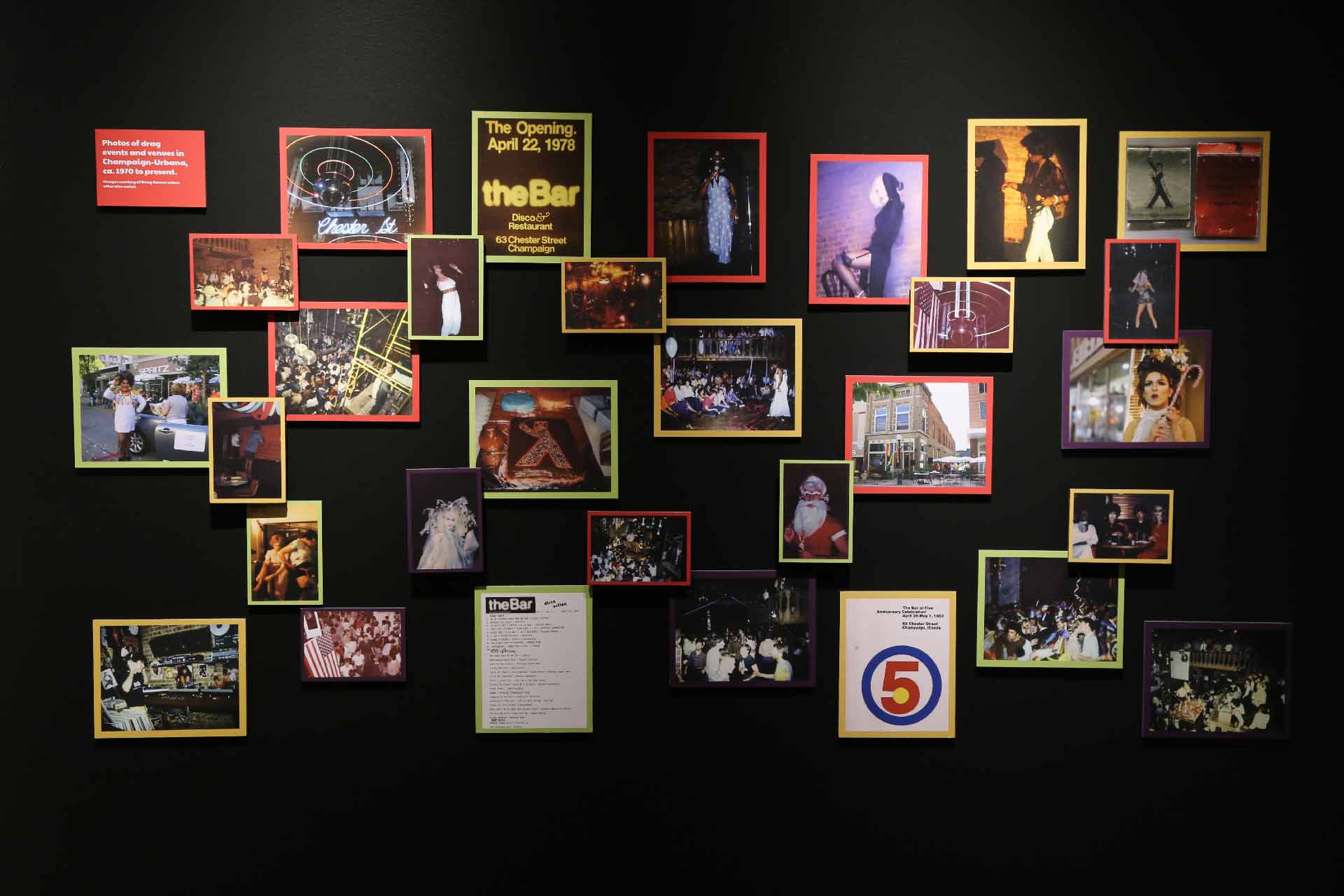 black wall with many photographs of drag events and other relevant imagery