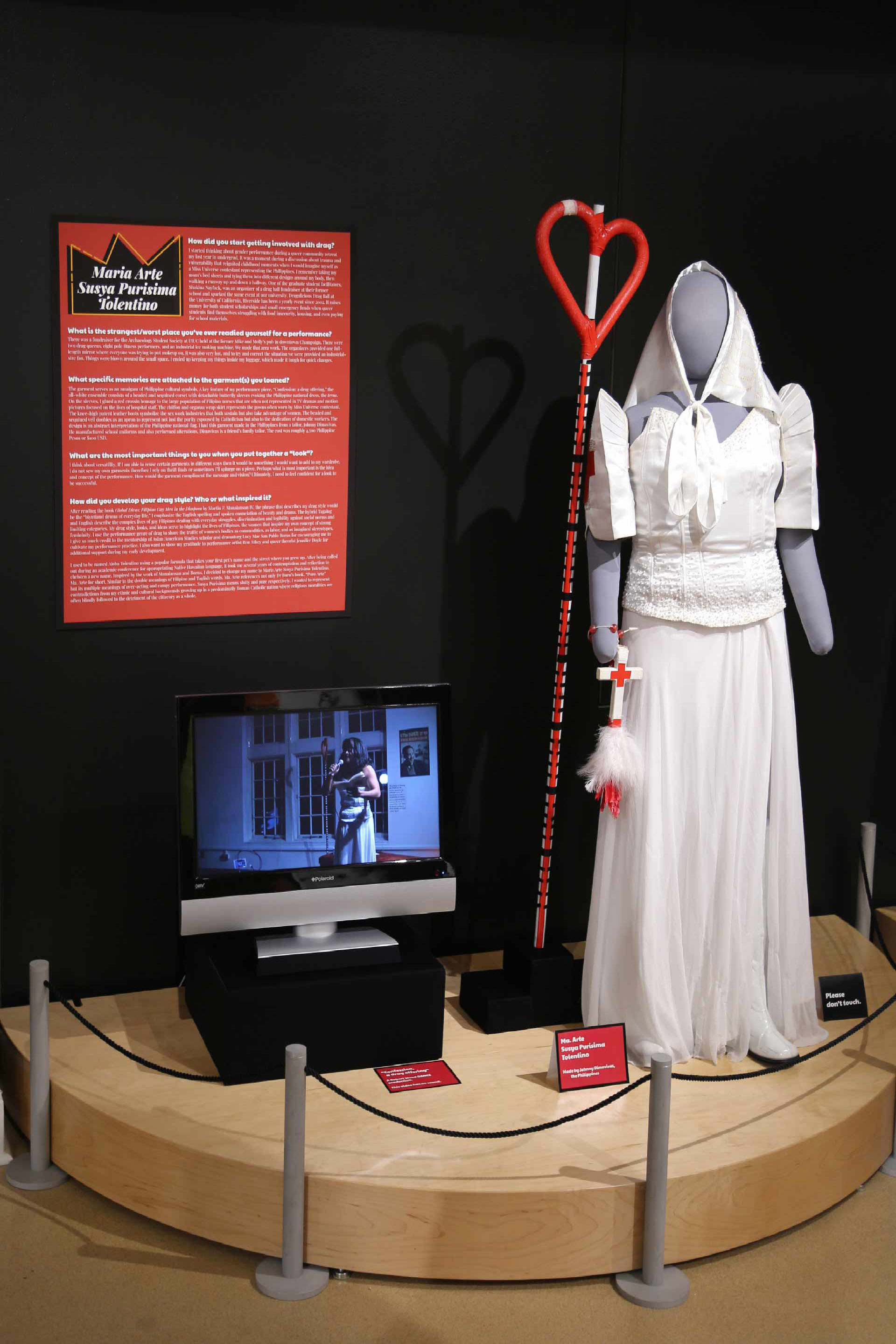 Mannequin in nurse drag costume display next to TV displaying video