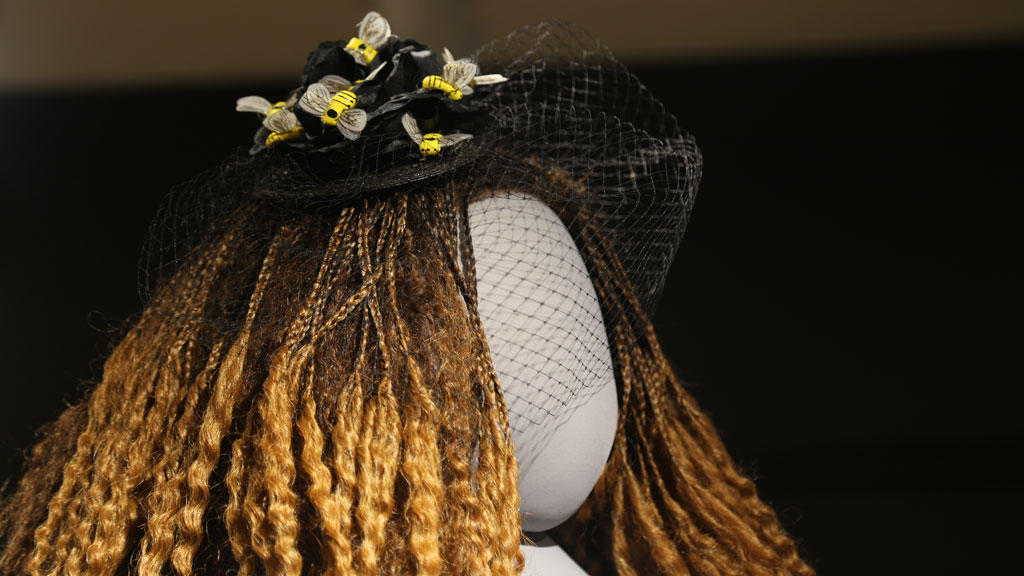 closeup of head of mannequin with a hat with a veil and bees attached