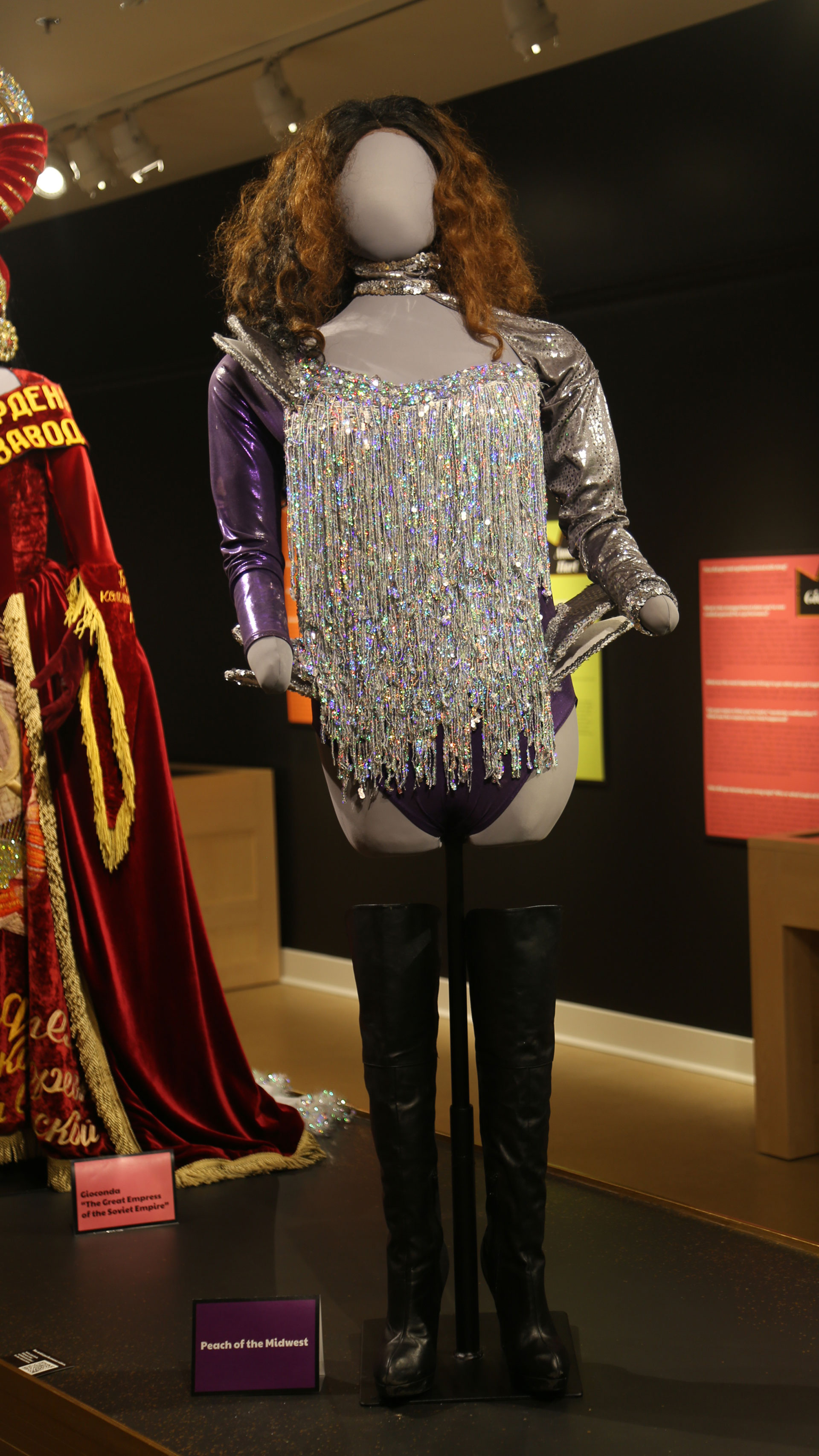 full view of mannequin with a sparkly costume with one purple sleeve with black boots