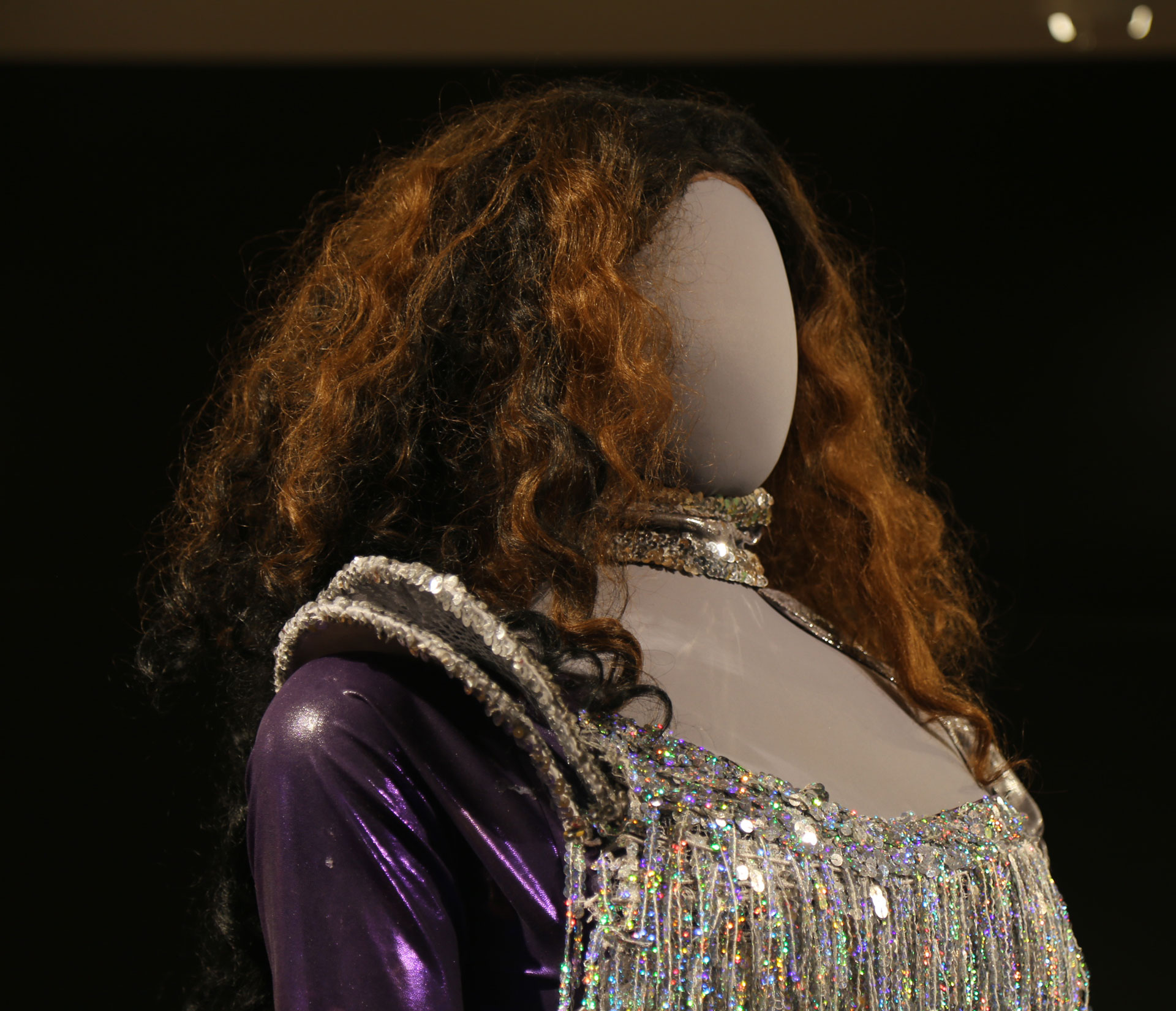 diagonal view of mannequin head with curly hair and sparkly costume with purple sleeves