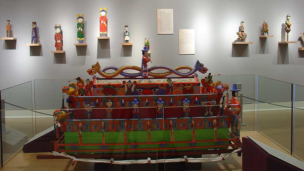 people on a dragon boat, figure sculptures arranged on the wall