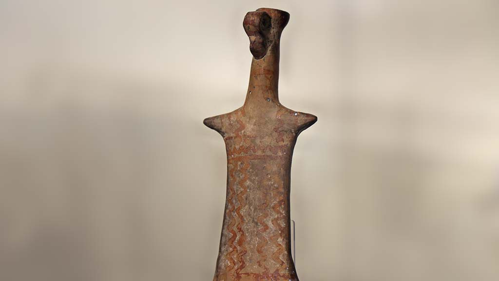 heavily stylized terracotta figure with a long neck and very short arms