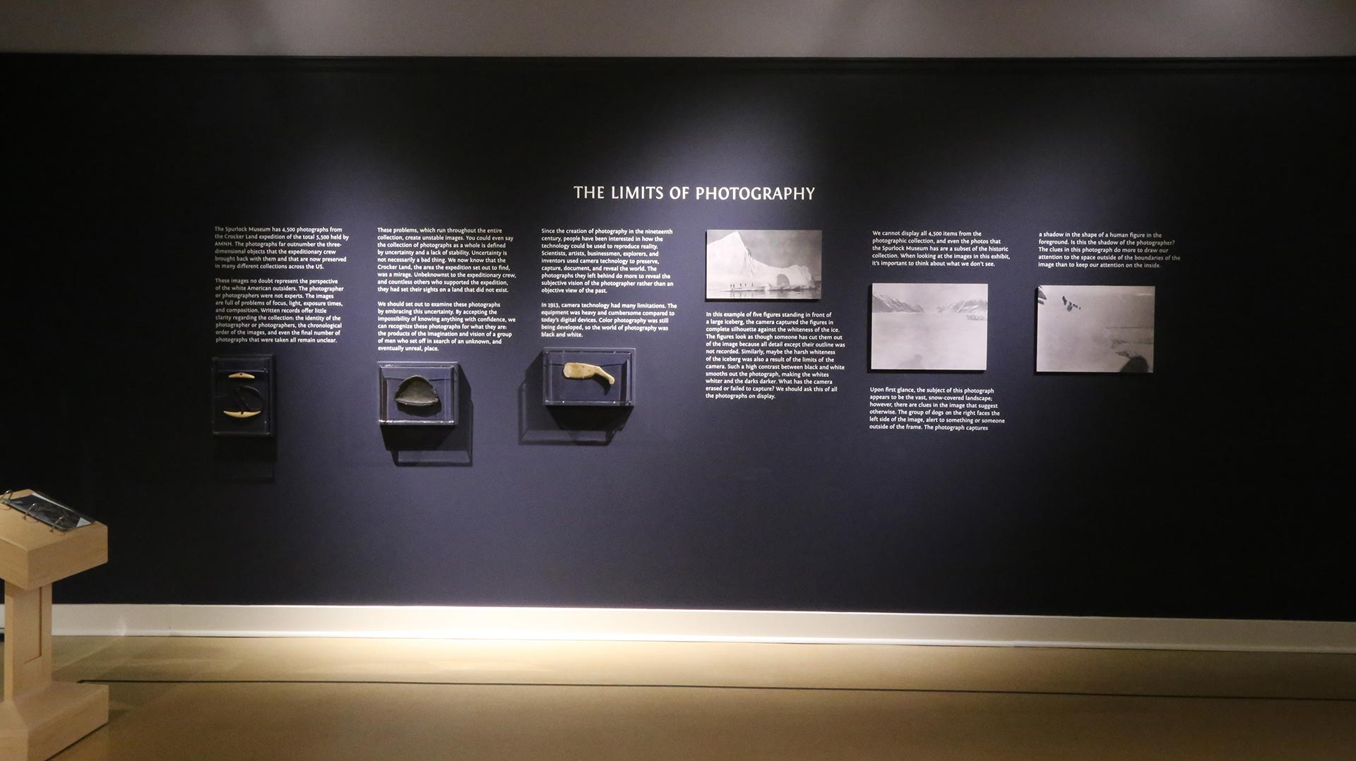 artifacts and photos on the wall aligned with text about the limits of photography