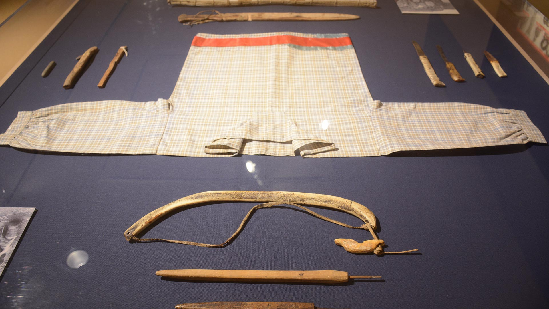 hooded clothes with an orange strip, wooden tools in a display case