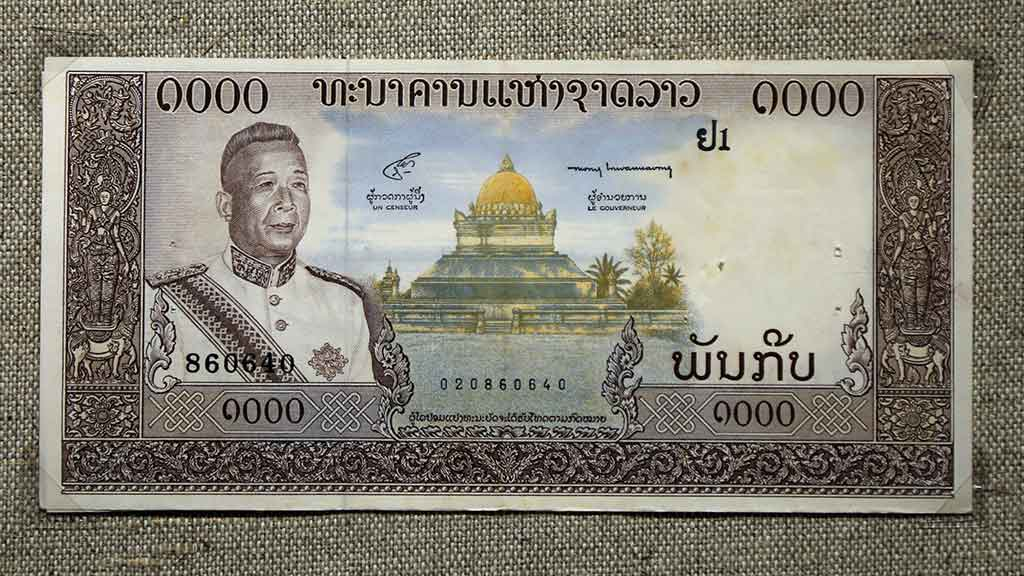 paper bank note showing Lao king and Buddhist stupa