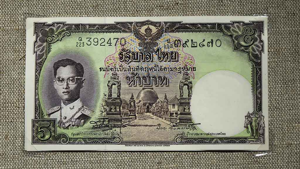 paper bank note showing Thai king and Buddhist temple
