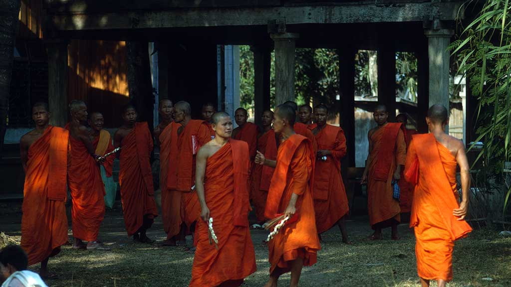 monks in orange robes convene outside of a temple