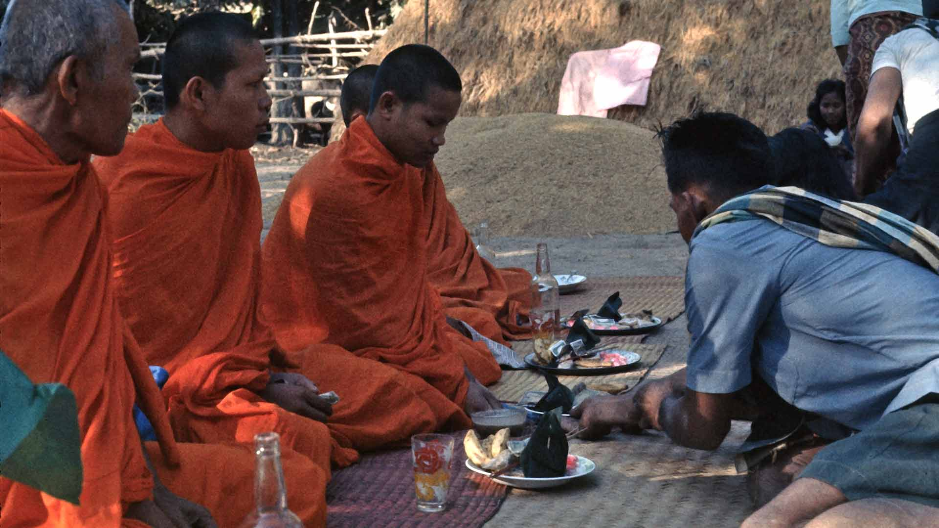 a man presents a dish of food to seated monks