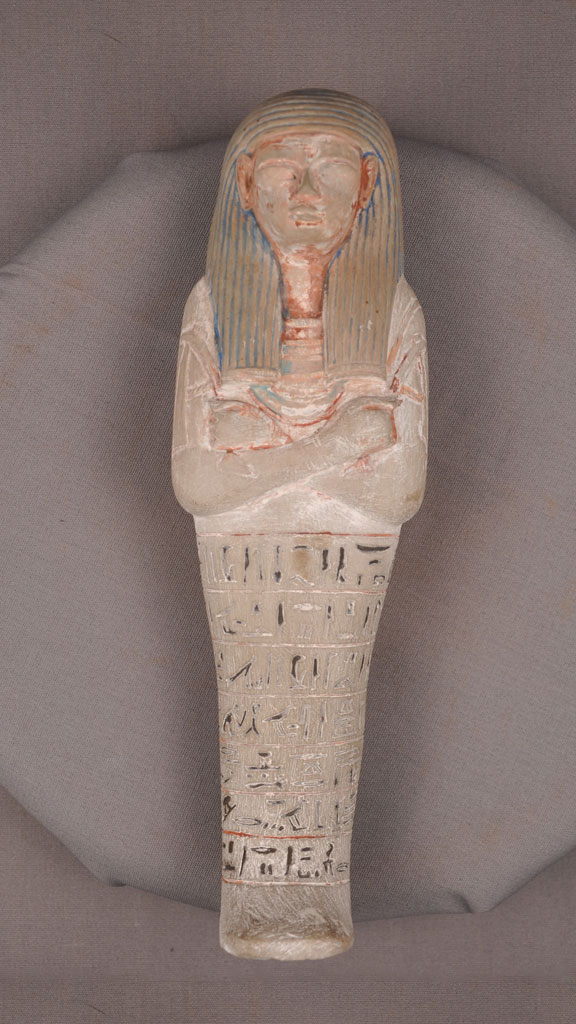 stone carving of a mummy with paint around the crevises