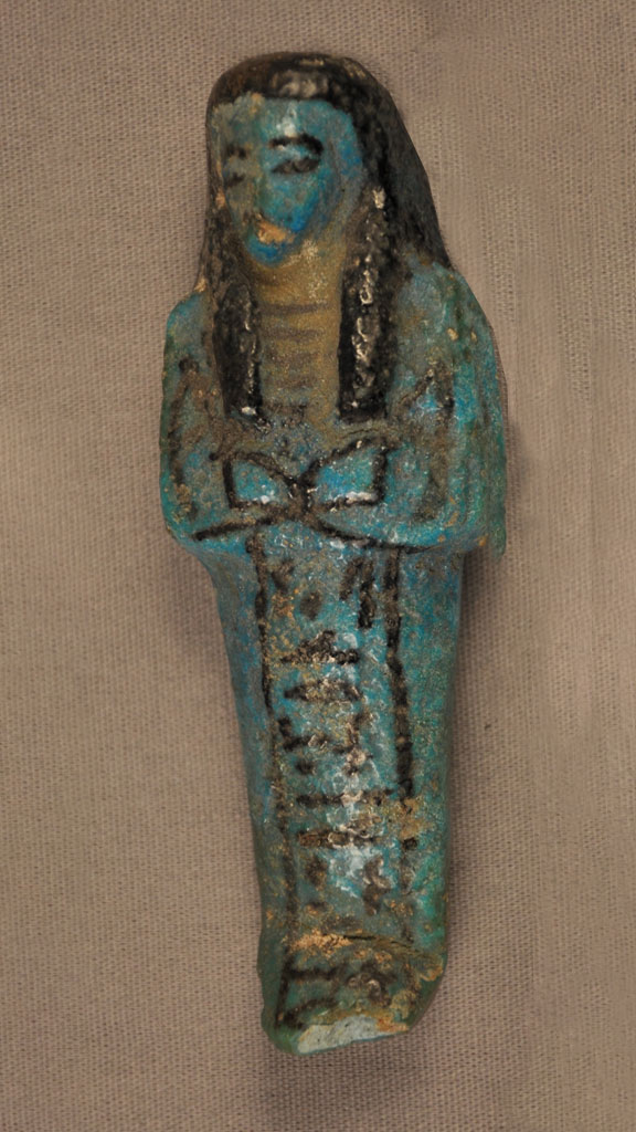 blue green stone carving of a mummy with black outlining