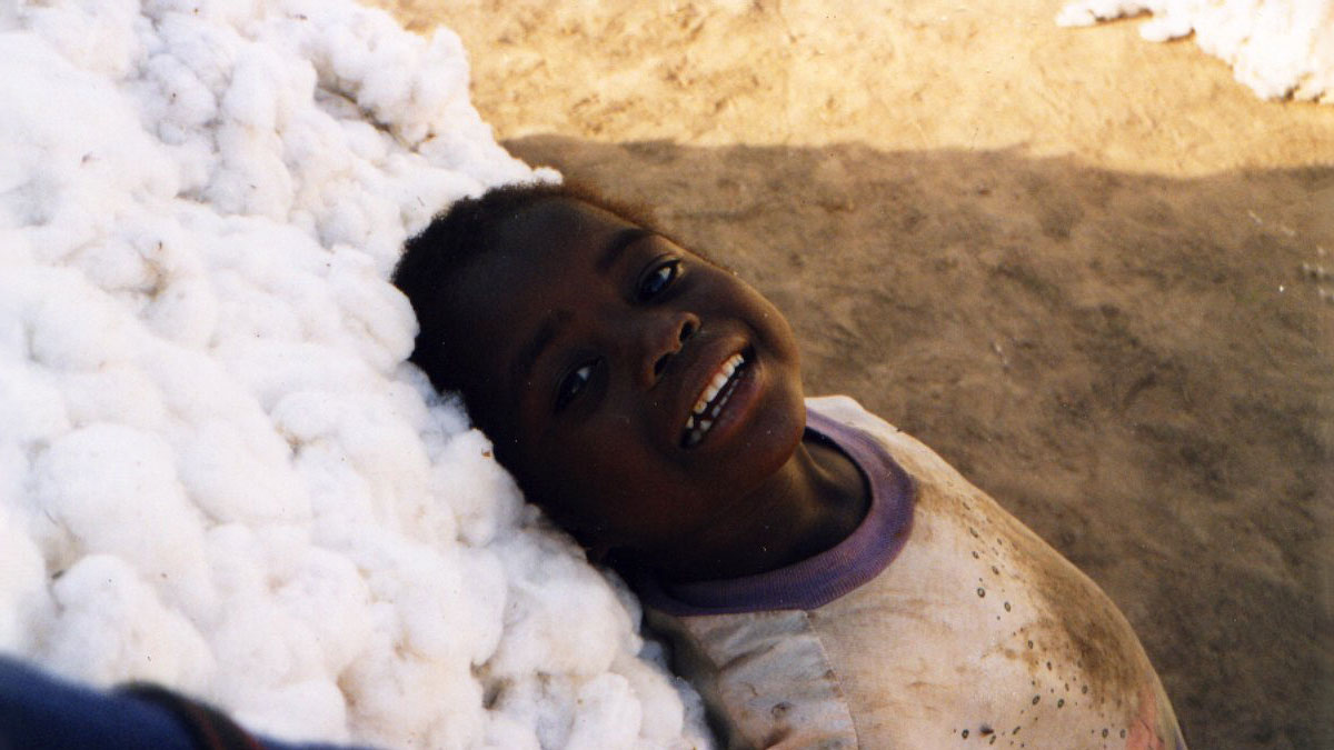 a child leaning against a mound of cotton