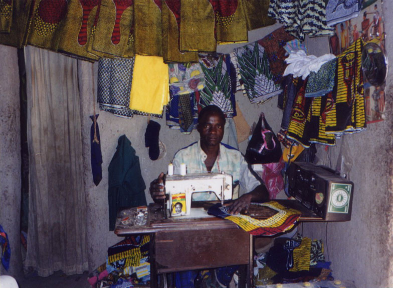 a tailor sitting at a sewing machine surrounded by vaious cloths