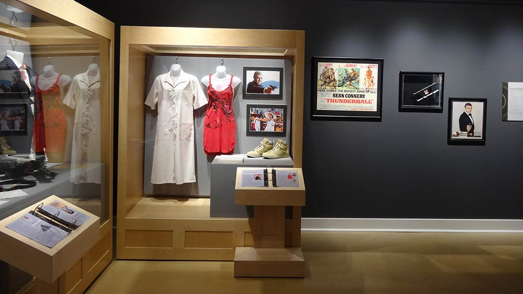 sleepshirt and red dress in display case, photos on the wall