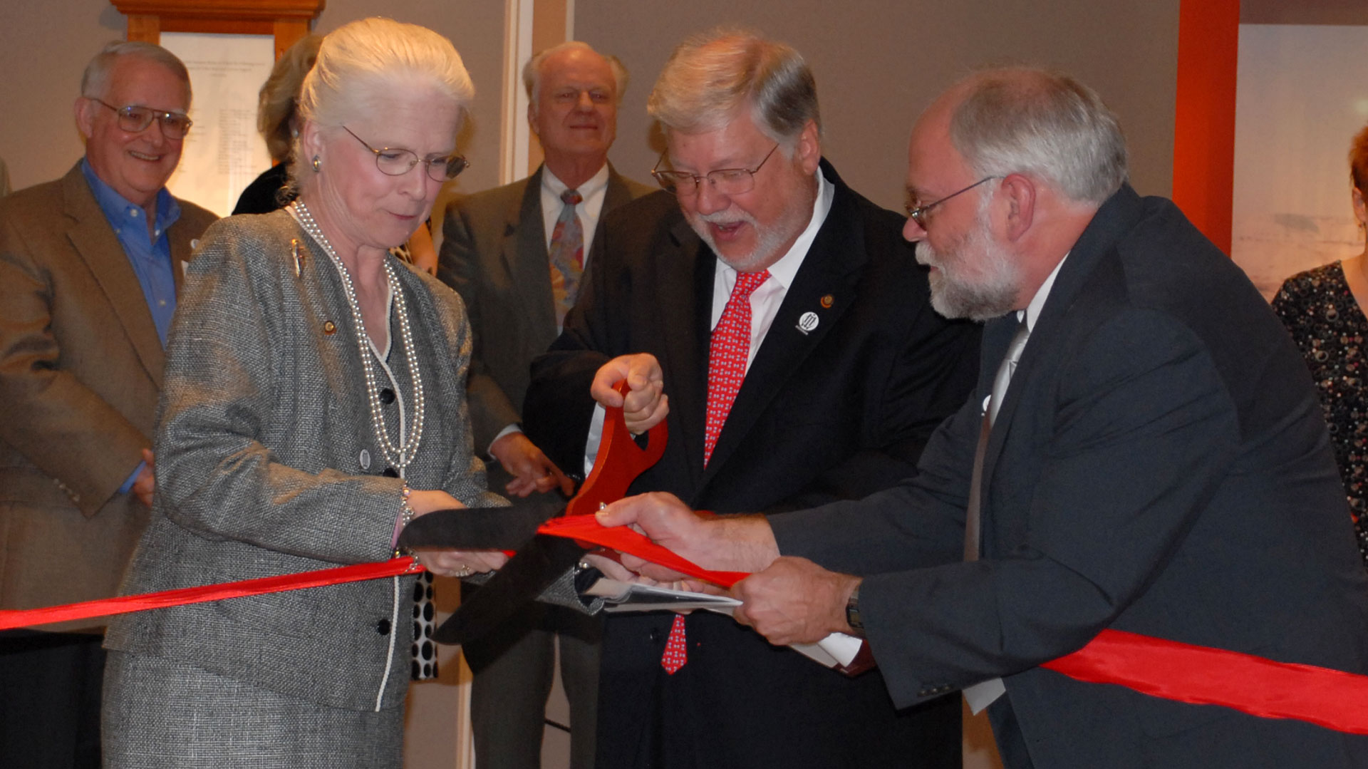 donors and Museum director cut red ribbon with large scissors