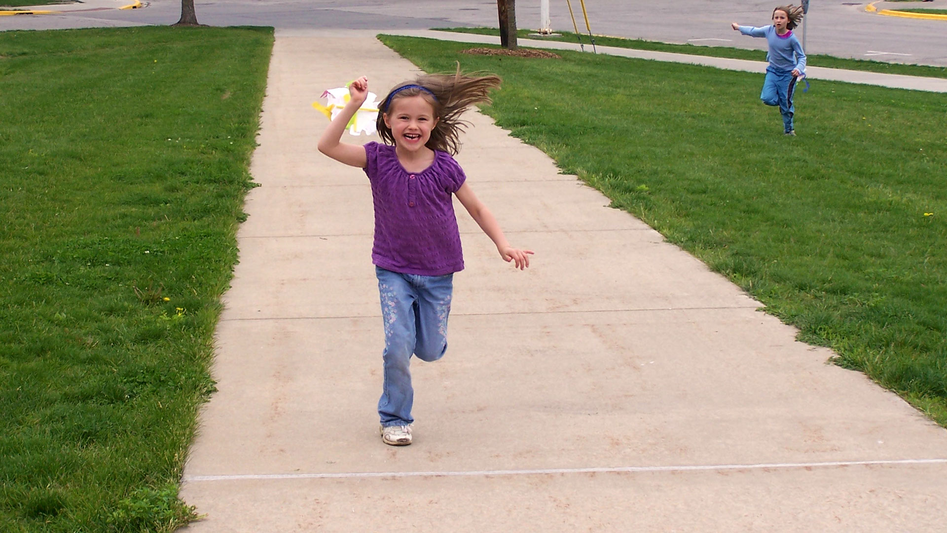 Enthusiastic child running outdoors towards you with a kite catching wind