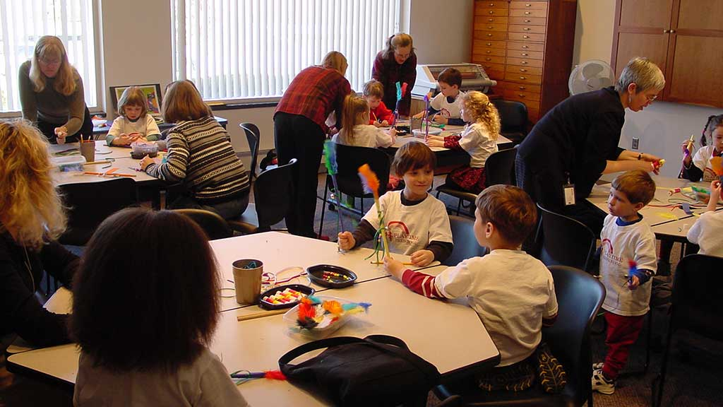 children and educators busily engaged in craft projects